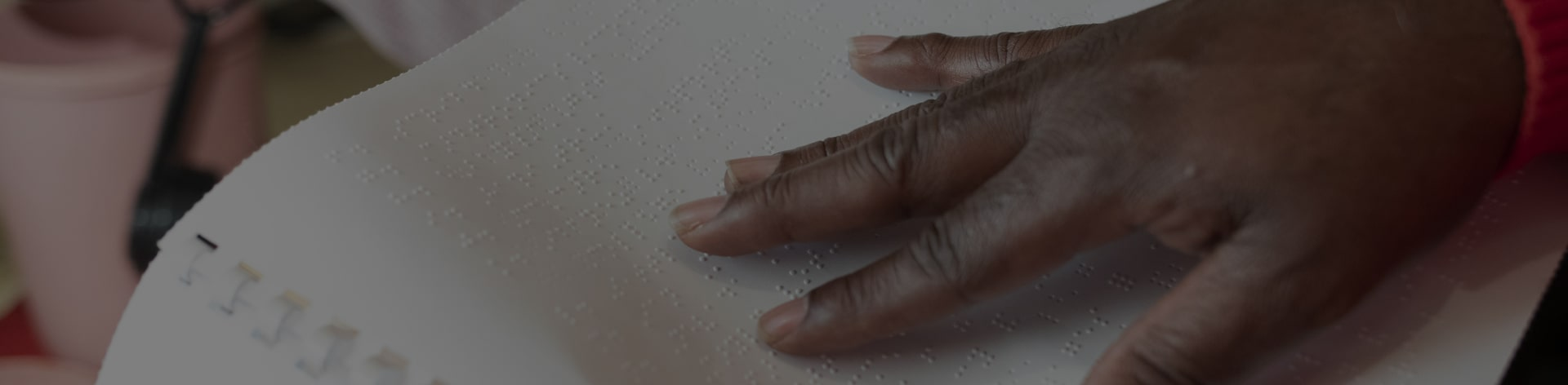 Picture of hand reading braille page.